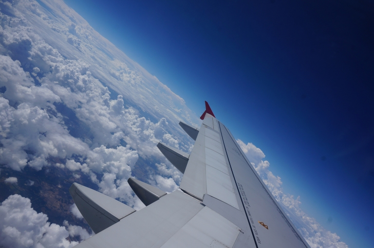 Airplane wing shot with clouds