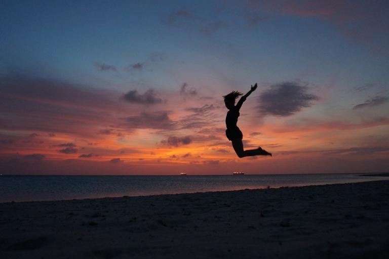 girl jumping silhouette sunset